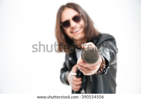 Cheerful young man with long hair in sunglasses giving a microphone and offering you to sing over white background - stock photo