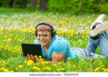 Cheerful young man working with a laptop and listening music on headphone outdoors - stock photo