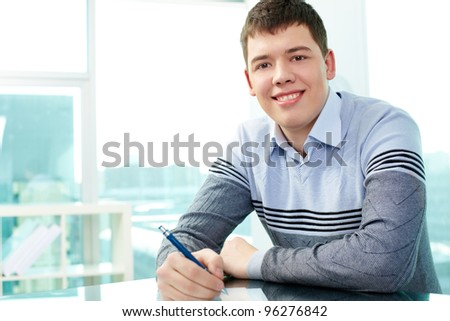 Cheerful young man working with documents - stock photo