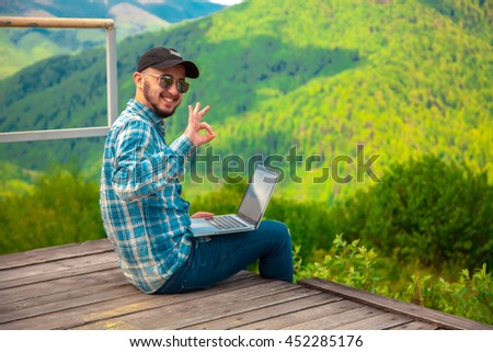 cheerful young man working with laptop on a high mountains smiling and showing OK - stock photo