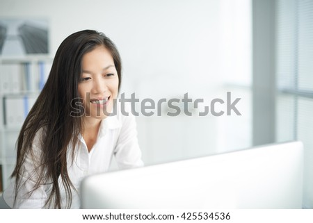 Cheerful young manager looking at computer screen