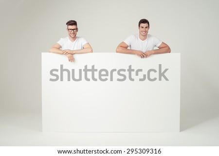 Cheerful Young Men Leaning on Blank Large White Board with Copy Space, Smiling at the Camera on Off-White Background. - stock photo