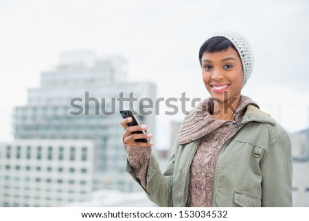 Cheerful young model in winter clothes holding her mobile phone outside on a cloudy day - stock photo