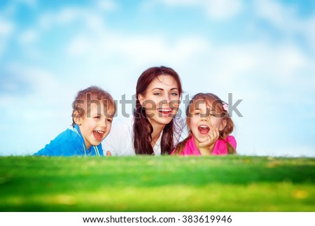 Cheerful young mother and her two precious kids having fun outdoors, lying down on fresh green grass field, happy family with pleasure spending time together - stock photo