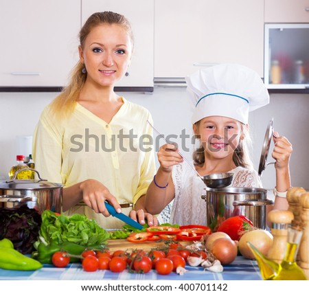 Cheerful young mother and little girl preparing vegetables in slow-cooker - stock photo