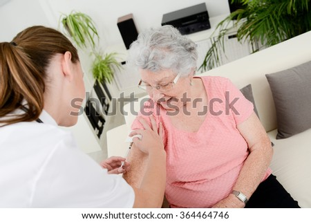 cheerful young nurse giving a vaccine injection to elderly woman at home - stock photo