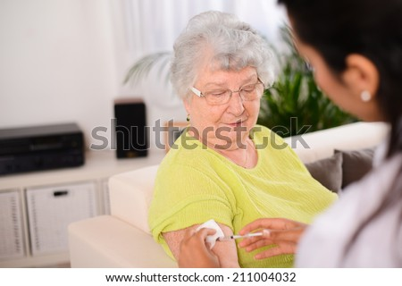 cheerful young nurse giving an injection to an elderly woman at home - stock photo