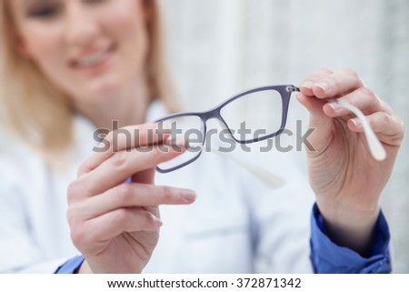 Cheerful young oculist is proposing new spectacles - stock photo