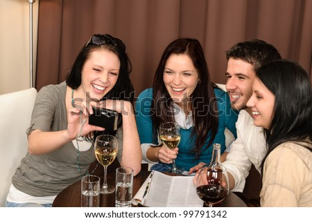 Cheerful young people enjoy drink after work at restaurant - stock photo