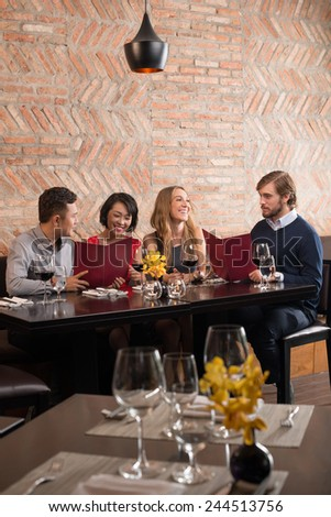 Cheerful young people in a restaurant - stock photo