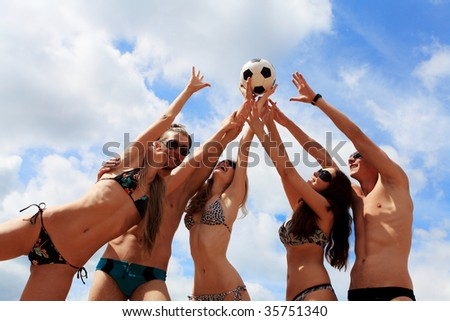 Cheerful young people playing volleyball on a beach. Great summer holidays.