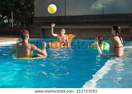 Cheerful young people playing with ball in swimming pool - stock photo