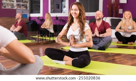 Cheerful young people studying new position at yoga school - stock photo