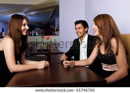 Cheerful young people talking at the table. Focus on women on the right - stock photo