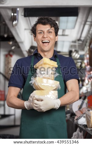Cheerful Young Salesman Carrying Cheese In Store