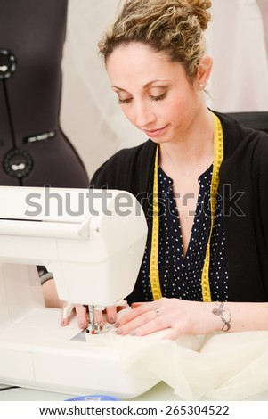 cheerful young seamstress sewing a wedding dress on her sewing machine - stock photo