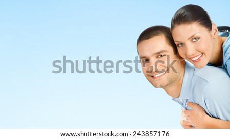 Cheerful young smiling amorous attractive couple, against blue sky background, with copyspace - stock photo