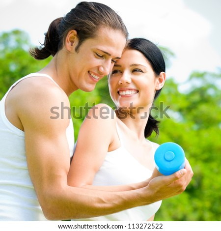 Cheerful young smiling couple with dumbbells on outdoor fitness workout