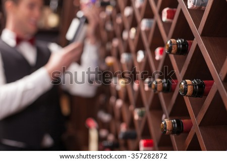 Cheerful young sommelier is choosing wine in cellar. He is smiling. Focus on bottles in shelf - stock photo