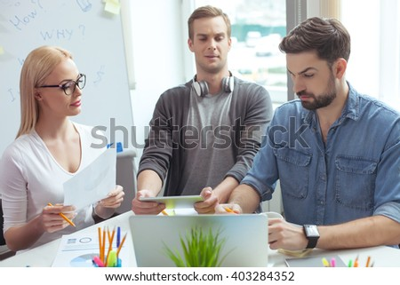 Cheerful young team using computer for work - stock photo