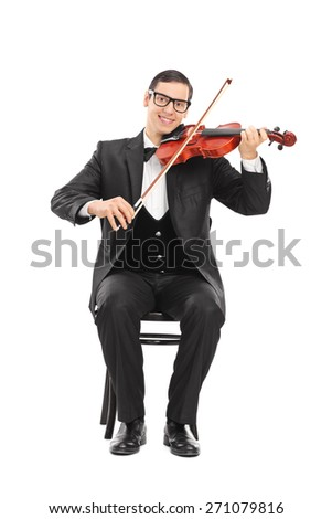 Cheerful young violinist playing an acoustic violin seated on a wooden chair isolated on white background - stock photo