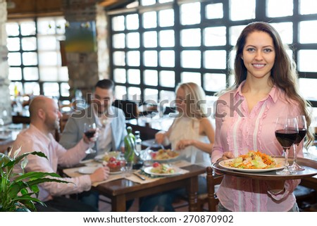 Cheerful young waiter serving restaurant guests at table   - stock photo