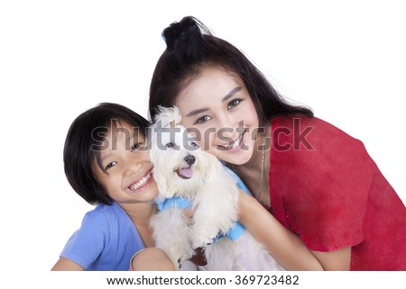 Cheerful young woman and her daughter holding a maltese dog in the studio, isolated on white background - stock photo