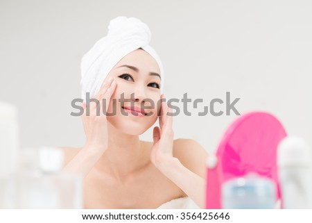 Cheerful young woman applying face moisturizer after shower - stock photo