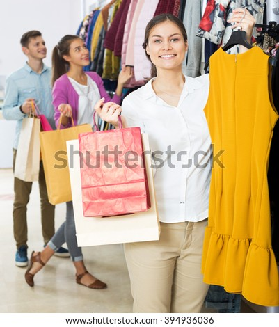 Cheerful young woman customers chooses liked things in the boutique