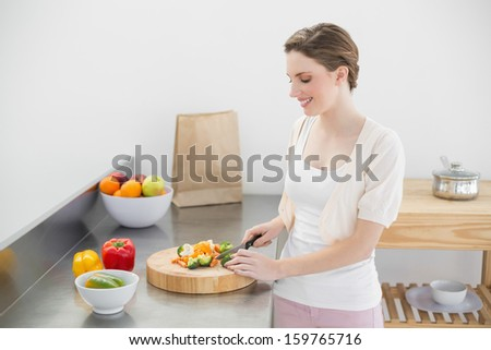 Cheerful young woman cutting vegetables while standing in her kitchen at home - stock photo
