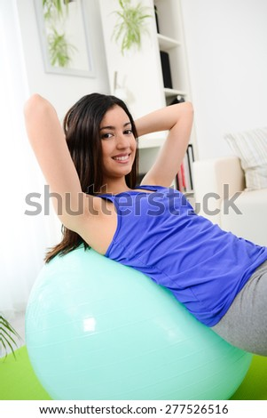 cheerful young woman doing fitness exercises at home - stock photo