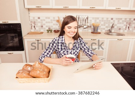 Cheerful young woman drinking coffee with cakes and reading news on tablet - stock photo