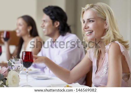 Cheerful young woman enjoying dinner party with friends - stock photo