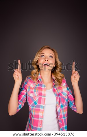 Cheerful young woman gesturing with fingers and looking up - stock photo