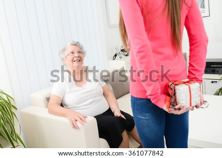 cheerful young woman handing a gift to elderly senior woman - stock photo