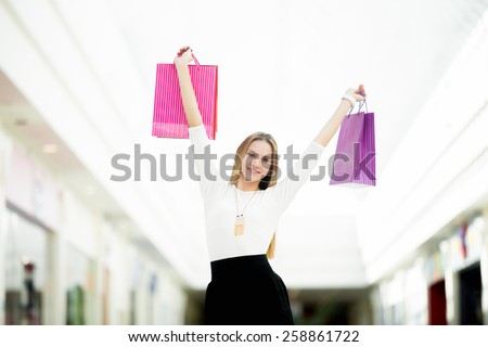 Cheerful young woman happy with her purchases, dancing with shopping bags. Sale, discount, fashion, profitable offer concepts - stock photo