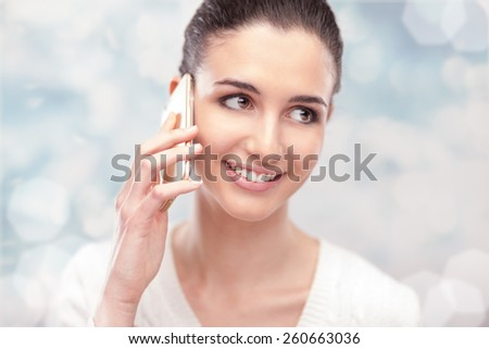 Cheerful young woman having a phone call with her smartphone and smiling  - stock photo