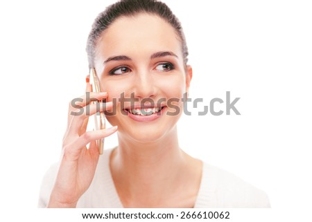 Cheerful young woman having a phone call with her smartphone and smiling on white background - stock photo
