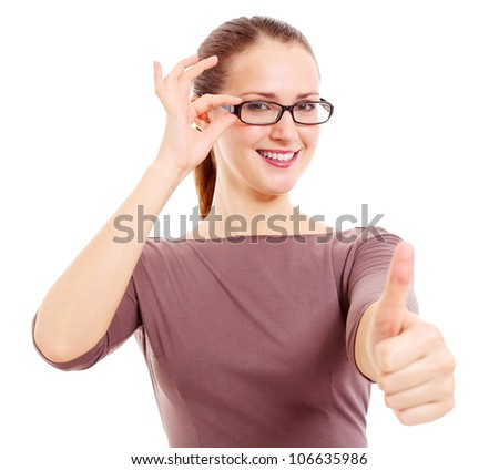 Cheerful young woman holding eyeglass frame and showing thumb up symbol. Isolated on white background, mask included - stock photo