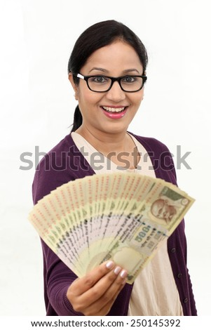 Cheerful young woman holding Indian rupee bills against white background - stock photo
