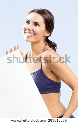 Cheerful young woman in fitness wear showing blank empty signboard with copyspace area for slogan or text, over grey background - stock photo