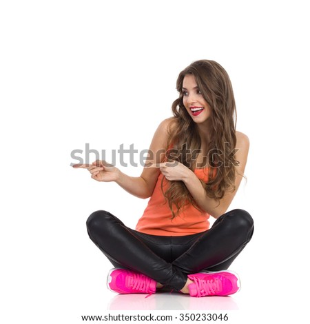Cheerful young woman in orange shirt, black leather trousers and pink sneakers sitting on a floor with legs crossed, pointing and looking away. Full length studio shot isolated on white.