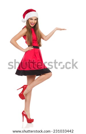 Cheerful young woman in santa's hat standing on one leg and presenting product. Full length studio shot isolated on white. - stock photo
