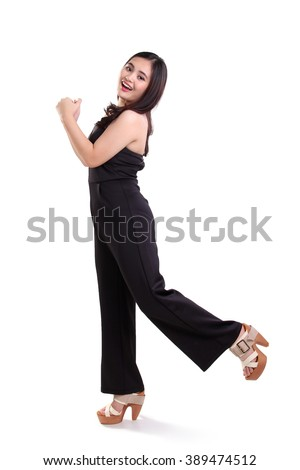 Cheerful young woman in stylish black clothes jumping, expressing happiness, full length portrait, isolated on white background - stock photo