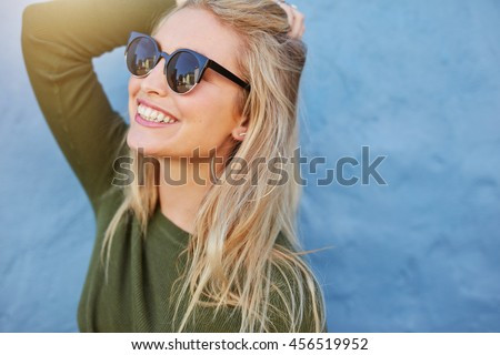 Cheerful young woman in sunglasses against blue background. Beautiful female model with long hair. - stock photo