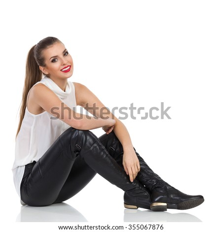 Cheerful young woman in white shirt, black leather trousers and boots sitting relaxed on a floor. Full length studio shot isolated on white - stock photo