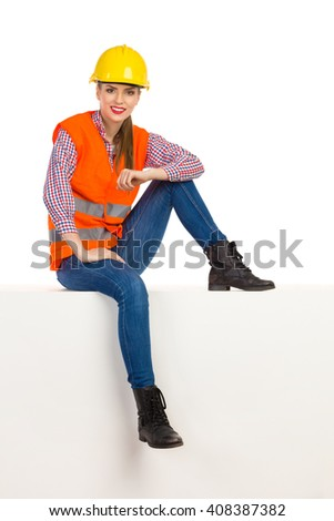 Cheerful young woman in yellow hardhat, orange reflective vest, lumberjack shirt, jeans, black boots, sitting relaxed on top and looking at camera. Full length studio shot isolated on white. - stock photo