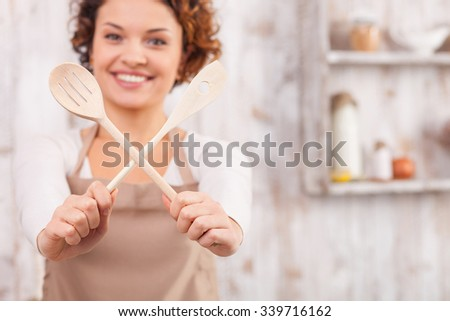 Cheerful young woman is cooking in the kitchen. She is holding two wood spoons and crossing them for fun. The lady is standing and smiling. Focus on utensil and copy space in right side - stock photo