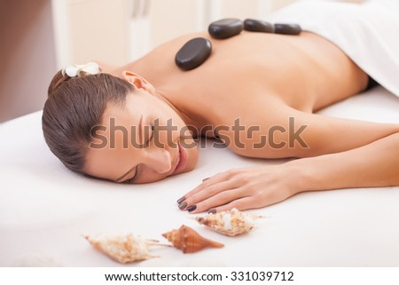 Cheerful young woman is enjoying massage at spa. She is lying with closed eyes. The girl is smiling with relaxation. She has special messaging stones on naked back - stock photo