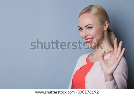 Cheerful young woman is gesturing positively - stock photo